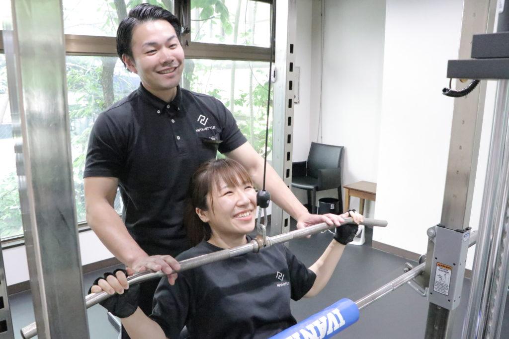パーソナルジムでトレーナーと一緒にトレーニングをする女性